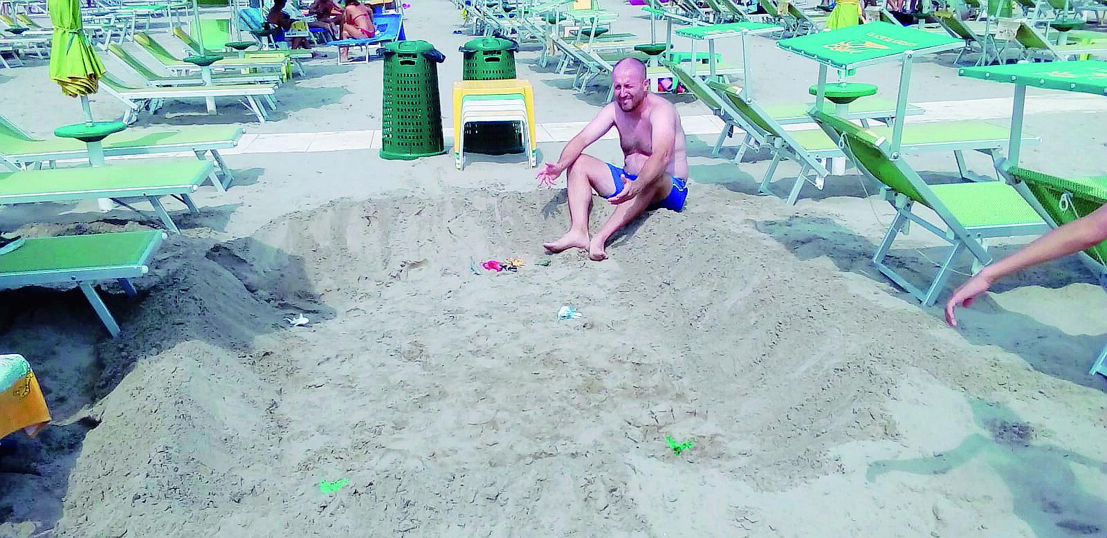 Misano, turista scava maxi buche in spiaggia. Bagnino chiama i vigili
