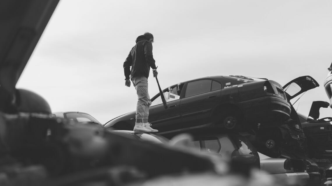 grayscale photo of woman standing beside car