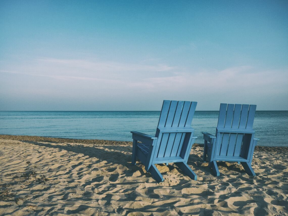 two blue beach chairs near body of water