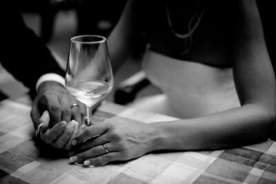 grayscale photo of man holding hand of woman holding wine glass
