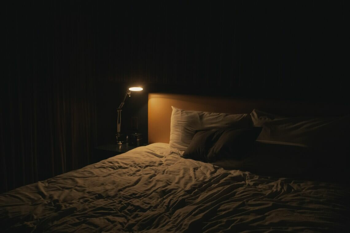 table lamp turned-on near bed