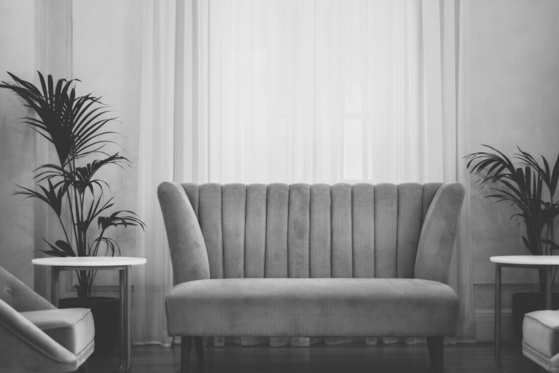 grey couch near white window curtain during daytime