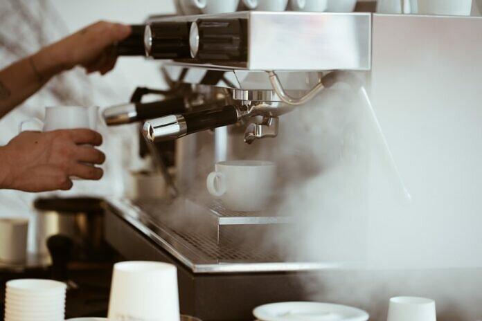 person holding white mug brewing coffee