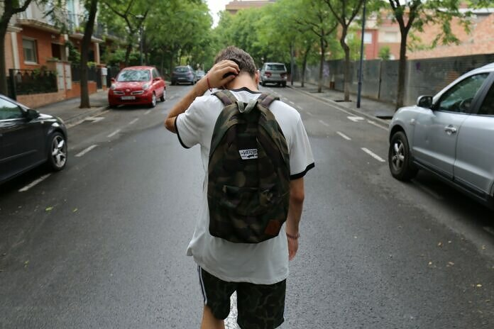 boy wearing white shirt and black shorts carrying backpack standing on black concrete road between vehicles and trees during daytime