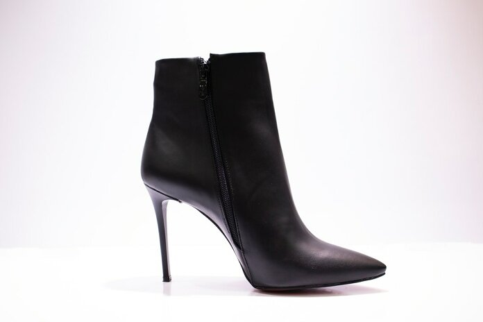 black leather boot on white surface