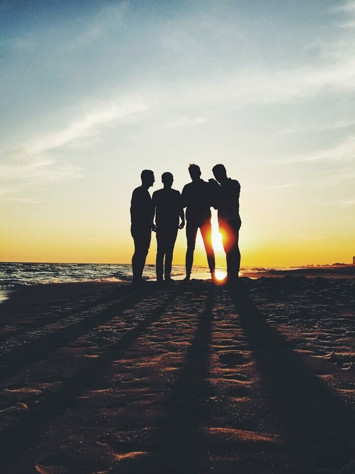 silhouette photography of four person standing on shore