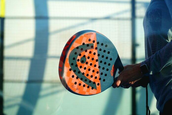 person holding orange and white polka dot round ball
