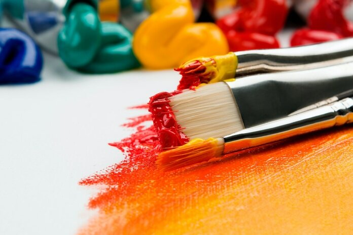 three silver paint brushes on white textile
