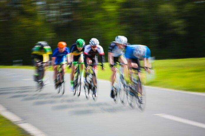 selective focus photography of cyclists on road during daytime