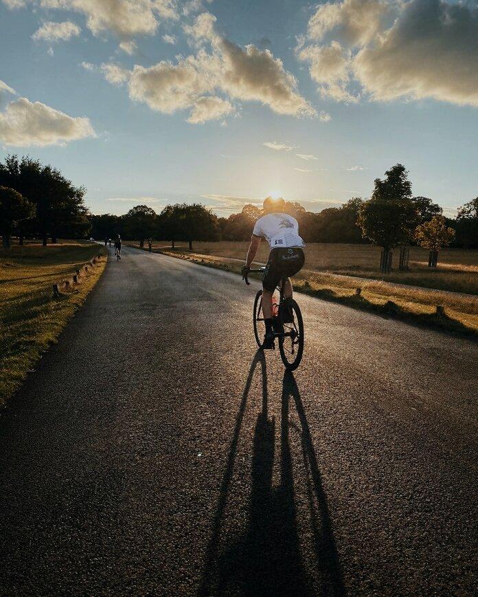 man in white shirt riding bicycle on gray asphalt road during daytime