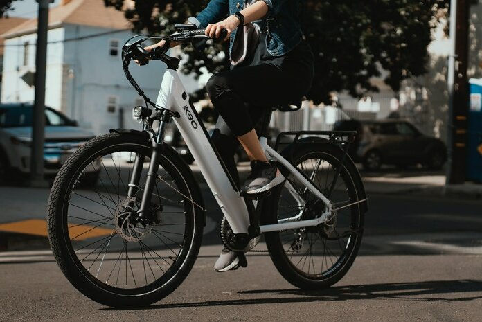 man in black jacket riding on white and black bicycle