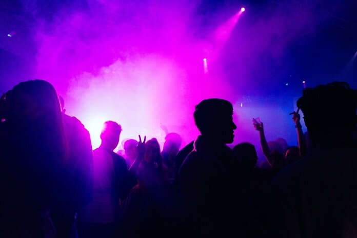 people standing on stage with purple lights
