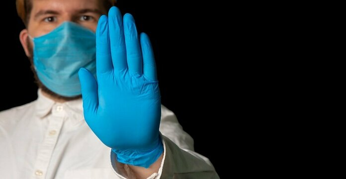 person in white long sleeve shirt covering face with blue textile
