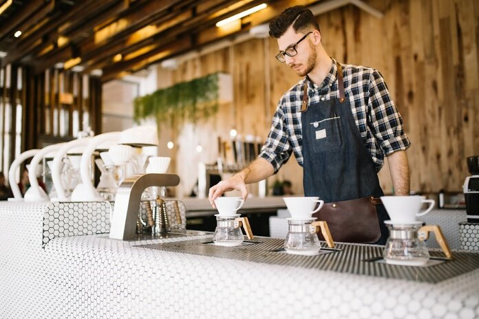 man in blue and white plaid button up shirt standing in front of table with mugs