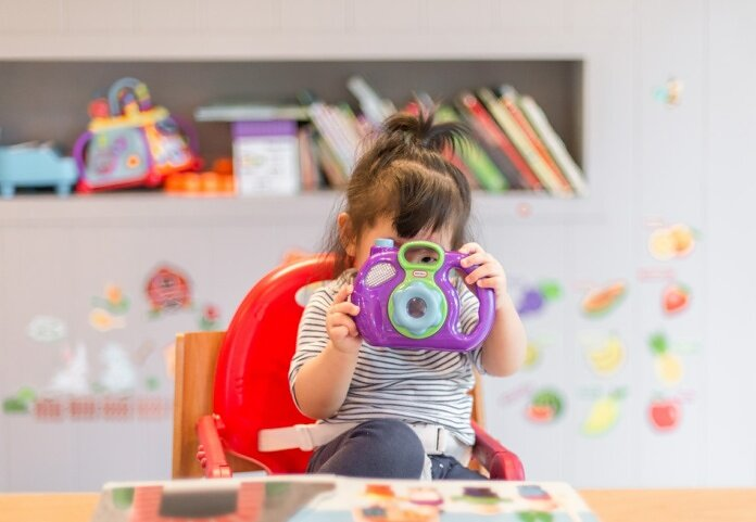 girl holding purple and green camera toy