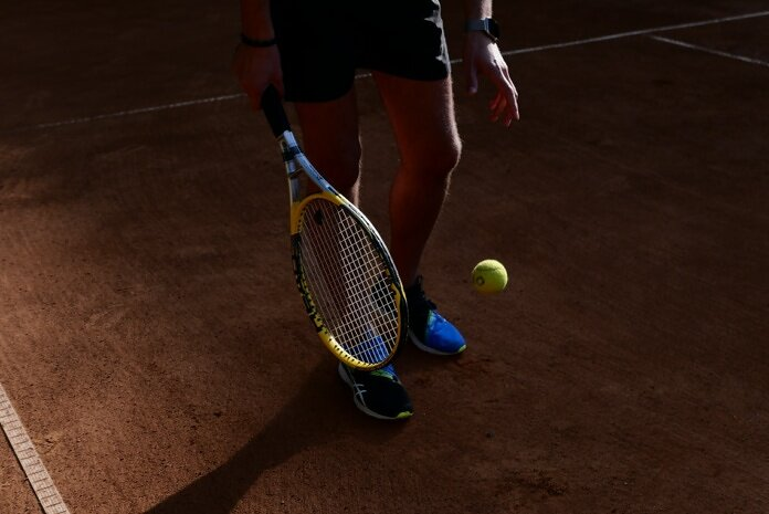 person in black shorts holding yellow tennis racket