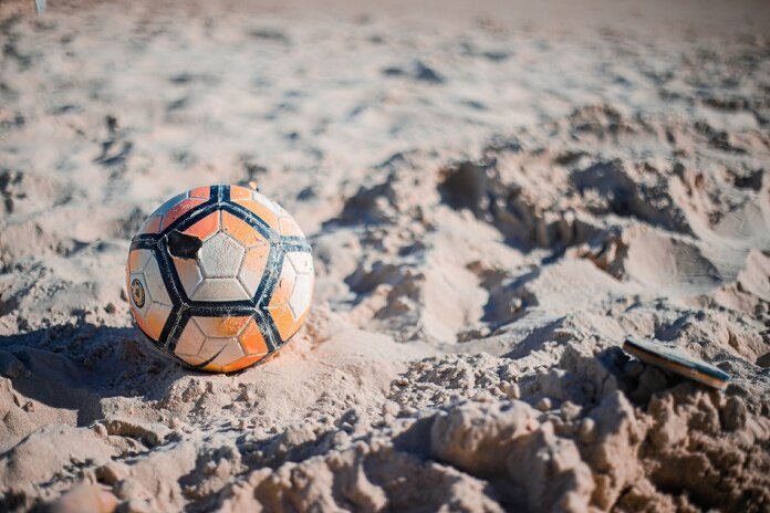 white and blue soccer ball on gray sand