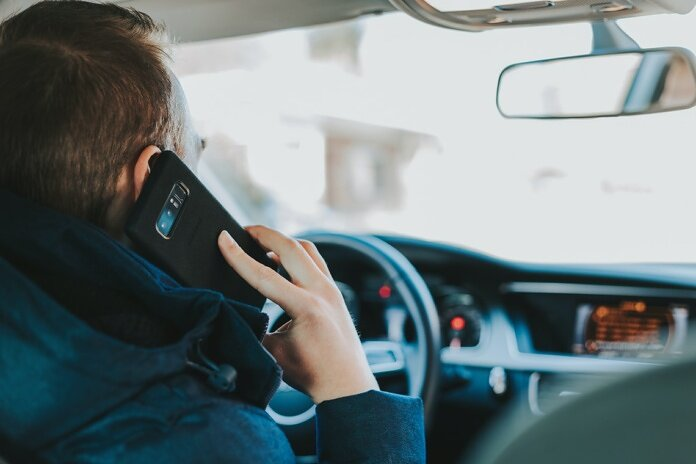 man sitting on car seat front of steering wheel holding phone