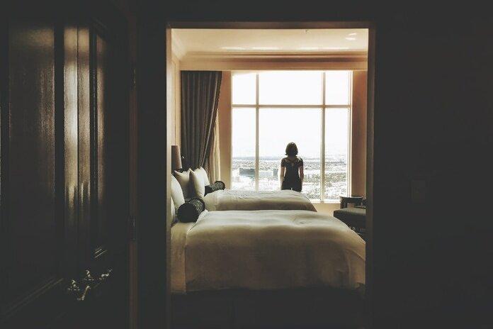 woman standing near window inside bedroom