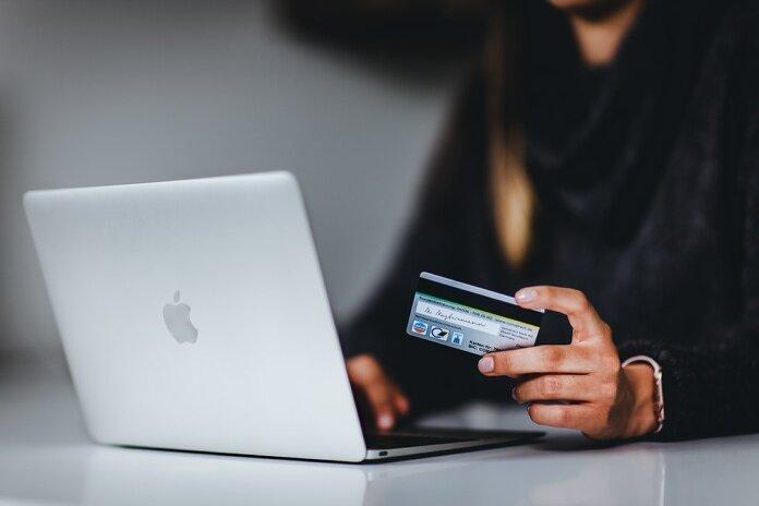 woman holding black smartphone near silver macbook