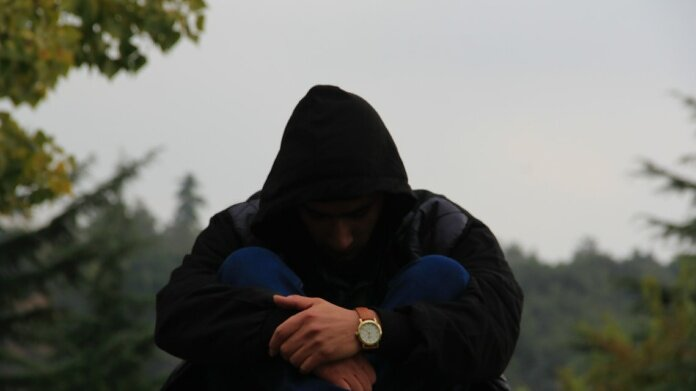 person in black hoodie and blue jacket