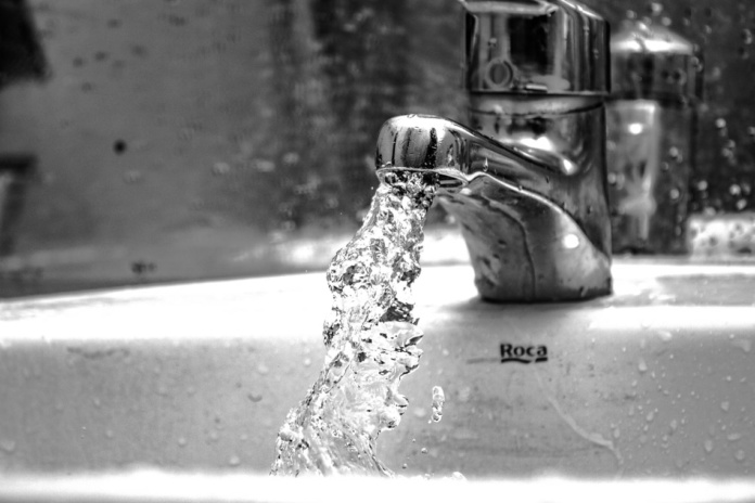 water falling from faucet in grayscale photography