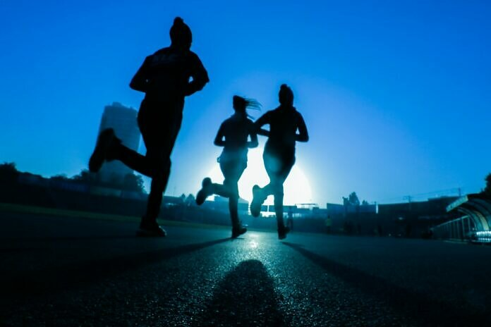 silhouette of three women running on grey concrete road