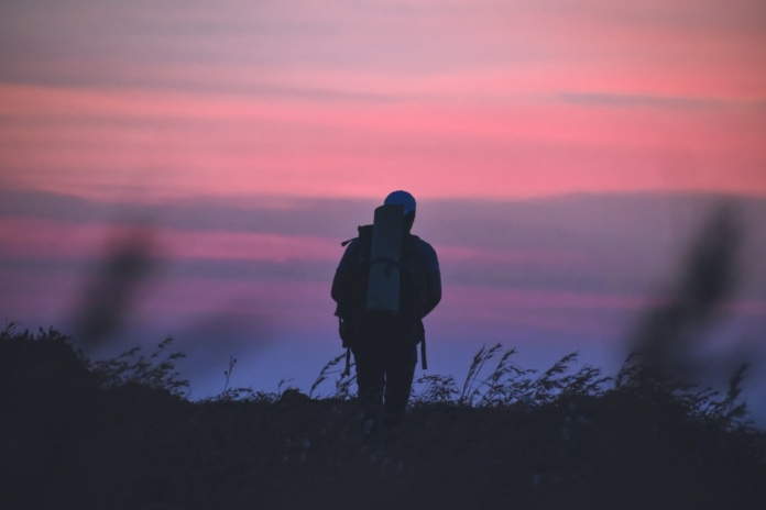 man in black jacket and black backpack standing on grass field during sunset