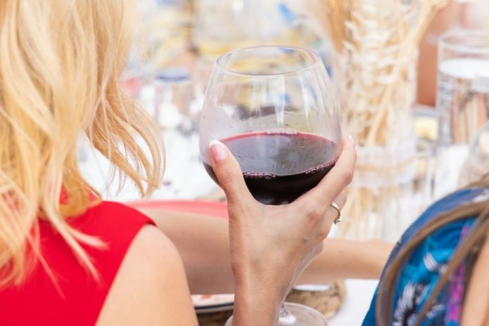 woman in red sleeveless top holding wine glass