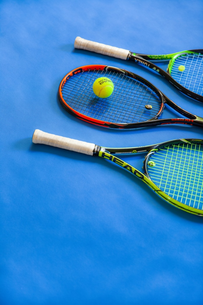 yellow and black tennis racket on blue textile
