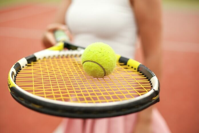green tennis ball on white textile