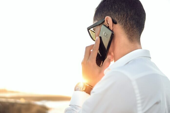 man holding smartphone standing in front of calm body of water
