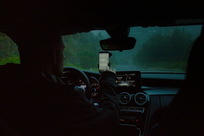 person driving a car using a phone