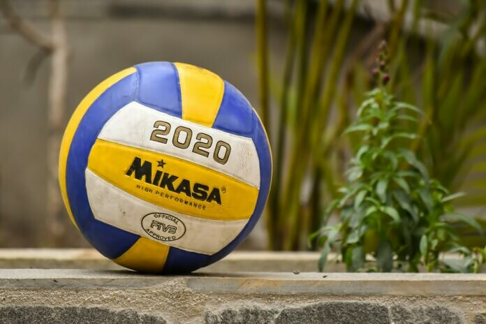 yellow and blue volleyball on brown wooden fence