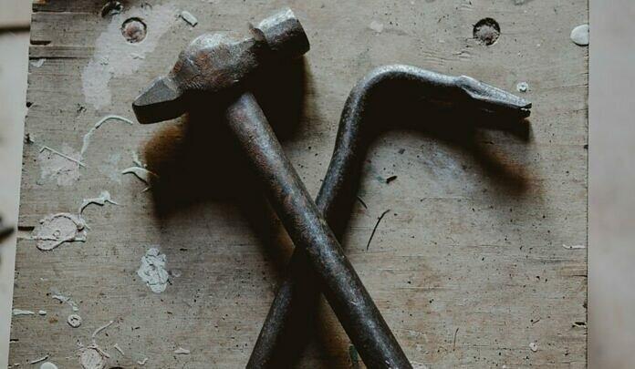 grey ball peen hammer and crow bar on brown wood