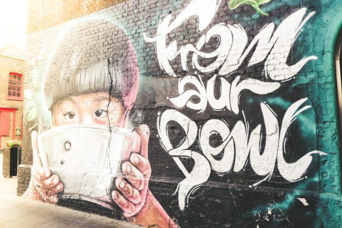 boy holding bowl graffiti wall during daytime