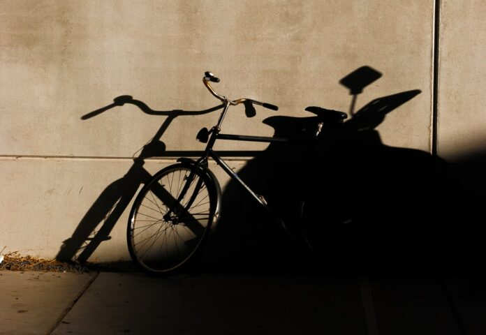 black bicycle leaning on wall