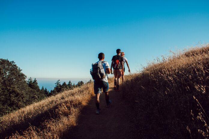 three person hiking on mountain